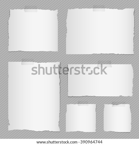 Pieces of torn white squared notebook paper with sticky tape on gray background