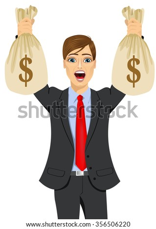 portrait of young businessman surprised holding two big dollar money bags