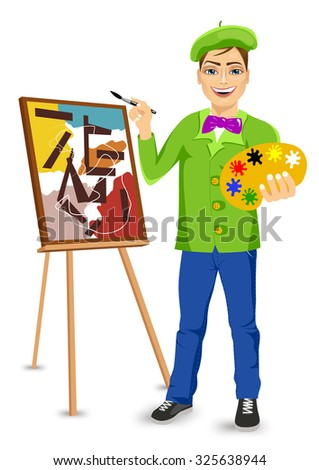 portrait of  young happy male painter artist smiling and painting with colorful palette standing near easel