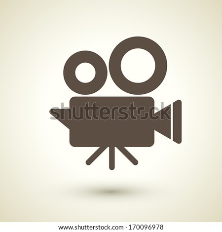 retro style cinema camera icon isolated on brown background