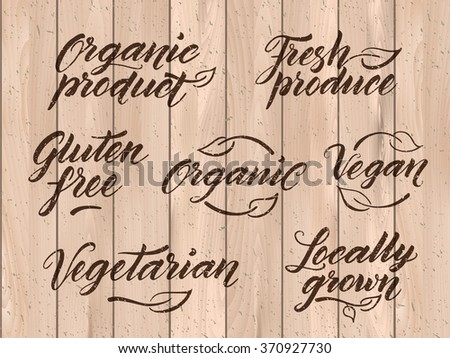 Retro styled healthy food letterings. Label, logo template stylized with stamp effect on a wooden background. Eps 10 vector. Texture can be easily removed.