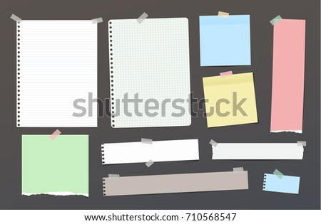Ripped blank ruled note, notebook, copybook paper strips, sheets stuck with colorful sticky tape on dark background.