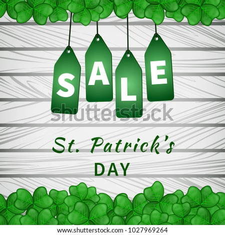 Sale poster of Saint Patrick's day with shamrocks on light wooden background and hanging green tags. Vector illustration