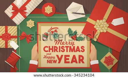 Santa Claus wrapping Christmas gifts and holding a box with wishes and decorations inside, top view - stock vector