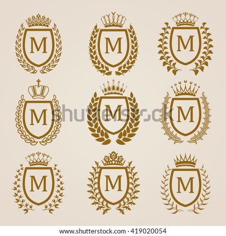Set of luxury golden shields with laurel wreaths, crowns. Royal heraldic elements, emblems, icons, symbols, labels, badges, blazons, monograms for web, page design. Vector illustration EPS 8. - stock vector