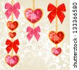 Shiny ruby heart pendants hanging on golden chains with colorful bows on floral background - stock photo