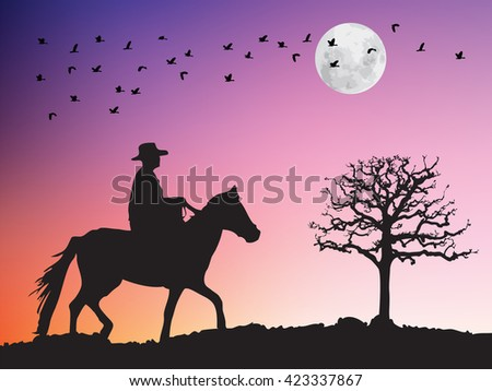 Silhouette of cowboy riding horse to dry tree and flying birds at sunset.
