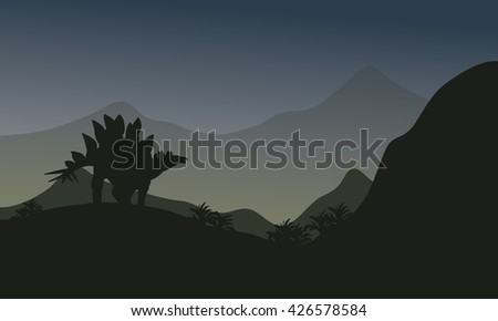 Silhouette of stegosaurus in hills at the night