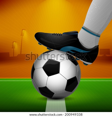 Soccer ball and cleats on grass background