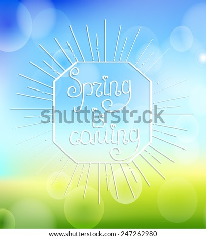 Sunburst with a calligraphical inscription of It's spring is coming on an abstract spring boceh background. - stock vector