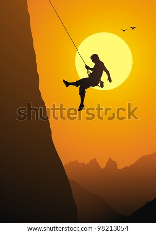 The climber goes down from the rock on a rope