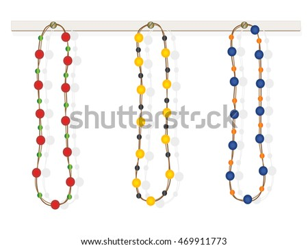 Three colorful necklaces on white wooden board