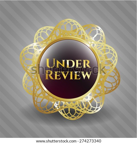 Under review gold shiny badge - stock vector