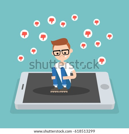 Upset crying nerd sitting on the mobile's screen and hugging his knees surrounded by the dislike symbols / editable flat vector illustration, clip art