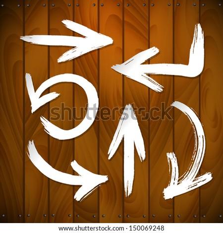 vector arrows on wooden plank background. brush stroke - stock vector