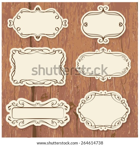 Vector illustration of a set of calligraphic frames with ornamental elements for scrapbook and other designs on wood background - stock vector