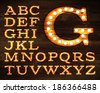 Vector of letters in retro style old lamp alphabet for light board on wood background. - stock vector