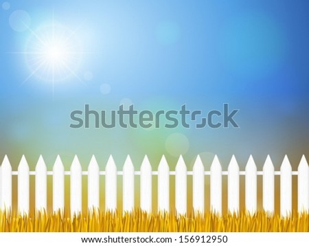 Wooden fence and autumn grass under sky.