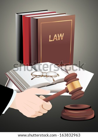 wooden gavel in hand and law books